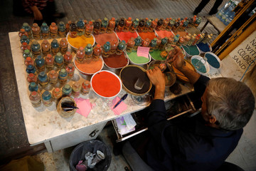 Palestinian craftsman Mohammed Al-Awawda creates coloured sand artworks at his souvenir shop in Hebron, in the Israeli-occupied West Bank