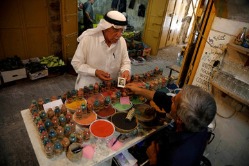 Palestinian man shows his picture to craftsman Mohammed Al-Awawda to create him a coloured sand artwork bearing his likeness at Al-Awawda's souvenir shop in Hebron, in the Israeli-occupied West Bank
