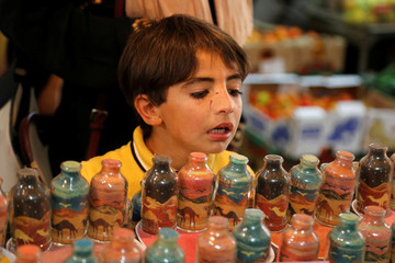 Boy looks at coloured sand artworks displayed at a souvenir shop owned by Palestinian craftsman Mohammed Al-Awawda, in Hebron, in the Israeli-occupied West Bank