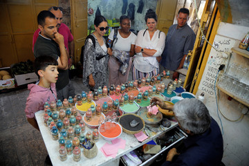 Tourists and locals look on as Palestinian craftsman Mohammed Al-Awawda creates coloured sand artworks at his souvenir shop in Hebron, in the Israeli-occupied West Bank