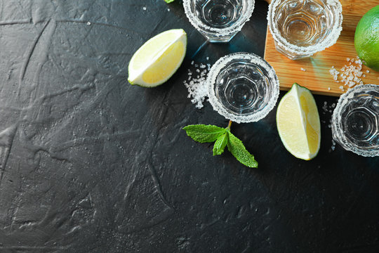 Tequila shots with salt, lime slices and mint on black table