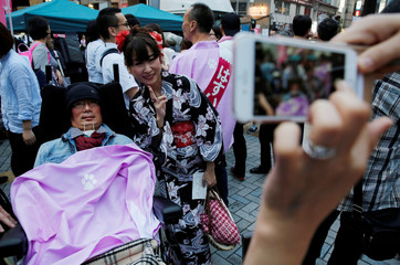 A woman takes a photo with Reiwa Shinsengumi's disabled candidate for Japan's July 21 upper house election Yasuhiko Funago, who has ALS, at his election rally in Tokyo