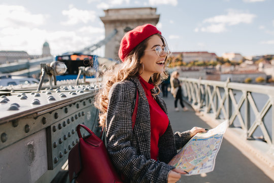 Spectacular european female tourist spending time in city, enjoying vacation. Outdoor photo of laughing young woman in gray coat walking around town and posing on bridge.