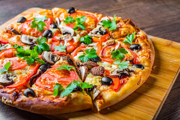 Cadres-photo bureau Pizzeria sliced Pizza with Mozzarella cheese, Tomatoes, pepper, olive, mushrooms, Spices and Fresh leaf. Italian pizza on wooden table background