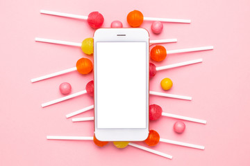 Mobile phone with pink and yellow candy on a pastel pink background