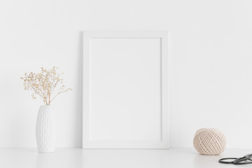 White frame mockup with workspace accessories  and gypshophila in a vase on a white table.Portrait orientation.