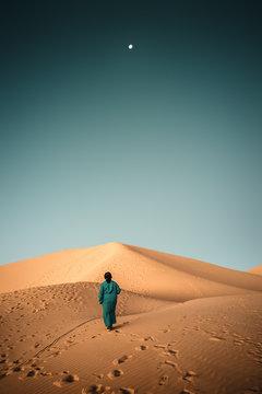 Rear view of woman walking on sand dune, Sahara, Morocco