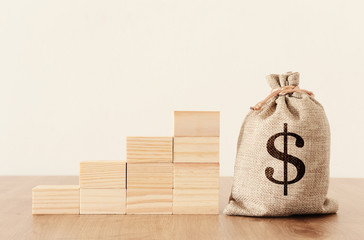 business image of a sack with money over wooden desk