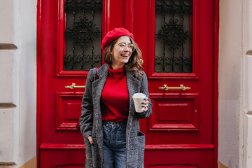 Glad white female model in long gray jacket looking away with smile standing near red door. Outdoor photo of beautiful caucasian woman in sweater drinks coffee in front of cafe and laughing. Fototapete