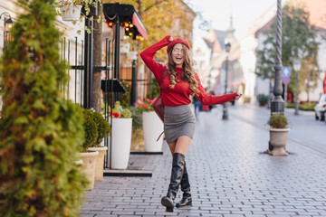 Magnificent caucasian girl in leather black shoes standing with legs crossed on pavement. Outdoor portrait of french female model in knee high boots posing in autumn day.