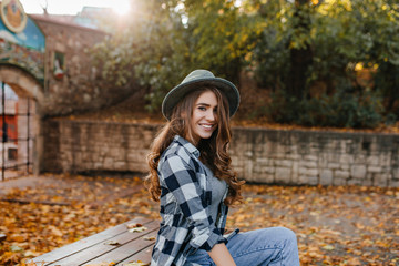 Wall Mural - Chilling white female model in blue checkered shirt spending autumn morning in park. Outdoor photo of smiling curly woman resting in warm october day, enjoying sunshine.