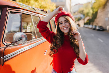 Amazing caucasian girl with curly brown hair spending time outdoor in sunny october morning. Photo of romantic lady with trendy manicure standing near her bus.