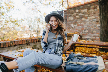Wall Mural - Resting white lady in short casual jeans calling someone on autumn background. Outdoor portrait of fashionable european girl in good mood enjoying coffee in november day.