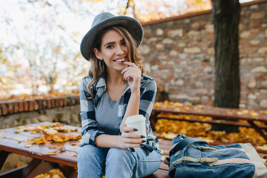 Interested young lady with cup of coffee posing in park in october day. Adorable woman in hat with black manicure spending time in yard in autumn morning.