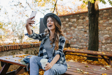 Positive woman with light-brown hair making selfie while drinking coffee in autumn park. Excited white lady in casual outfit relaxing in yard and taking picture of herself.