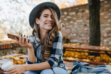 Pretty laughing girl with smartphone has a good time in autumn weekend. Outdoor portrait of lovable trendy lady with brown hair wears hat in october day. Wall mural