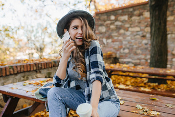 Wall Mural - Sensual curly woman in hat expressing funny emotions during photoshoot in autumn yard. Glad cute girl with light-brown hair looking away with smile, talking on phone.
