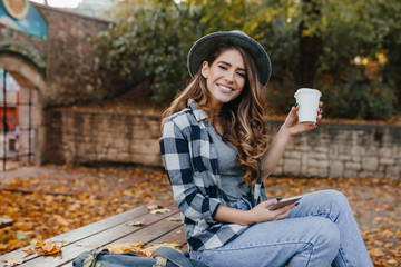 Wall Mural - Playful girl in blue jeans sitting on wooden table and enjoying good autumn day. Pretty caucasian lady with light-brown hair drinks latte in yard in october morning.