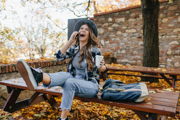 Fascinating young woman wears jeans laughing while talking on phone in park with yellow trees....