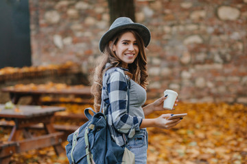 Wall Mural - Lovable white girl in checkered shirt holding smartphone and cup of coffee in september park. Romantic lady with backpack posing with smile in autumn yard.