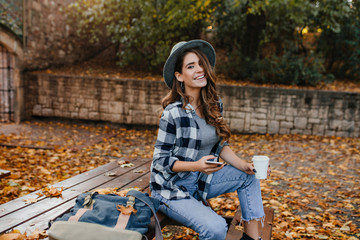 Wall Mural - Well-dressed laughing woman with light-brown hair sitting in park in october day and enjoying nature views. Cheerful white girl posing outdoor with yellow foliage on the ground.