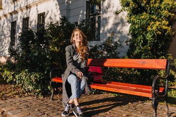 Wall Mural - Inspired girl in long coat sitting on wooden bench near her house early in evening. Outdoor portrait of blonde woman in jeans resting beside green trees in sunny october day.