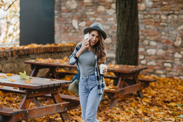 Wall Mural - Slim girl in blue denim pants talking on phone in park with trees behind. Outdoor photo of enthusiastic white woman in hat standing in the yard with cup of coffee.
