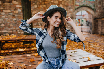 Wall Mural - Magnificent pale girl in trendy hat sitting on table in park and smiling. Adorable young woman with curly hairstyle playfully posing, enjoying autumn weekend.