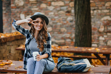 Wall Mural - Lovable white female model with curly hairstyle posing with peace sigh while drinks coffee in park. Autumn portrait of romantic european woman in checkered shirt.