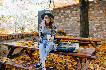 Wall Mural - Gorgeous slim lady wears short jeans sitting on table with legs crossed in autumn day. Glad curly woman in casual shirt drinks cappuccino during september photoshoot.