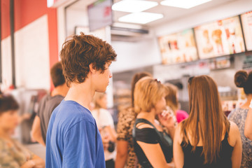 Fototapeta young teenager standing in a queue to receive the fastfood package obraz