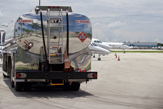 Tank truck on flight line with Jet A Fuel, no smoking, and hazmat placard on tank, air field with business jets blurred in background