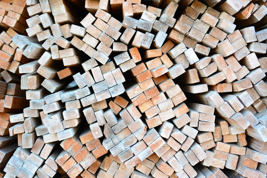 A large stack of wood boards in a lumber yard
