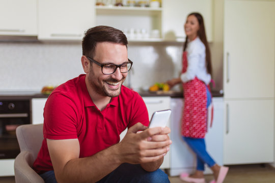Young couple in the kitchen. Man whilst checking mobile phone, woman preparing breakfast.