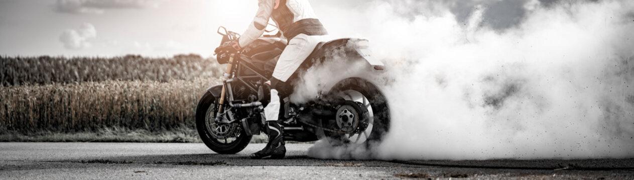 wilder Motorradfahrer lässt die Reifen bei einem Burnout durchdrehen und macht einen Donut