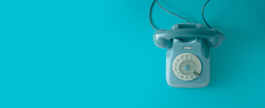 A blue vintage dial telephone with blue background.
