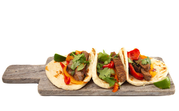 Three Fajitas on a Marble Serving Board on a White Background
