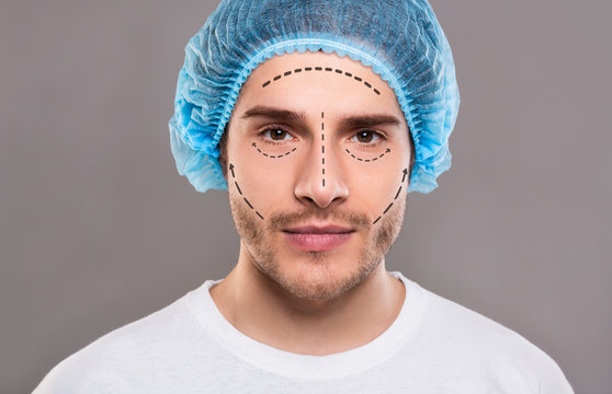 Handsome man in medical hat with pencil marks on skin