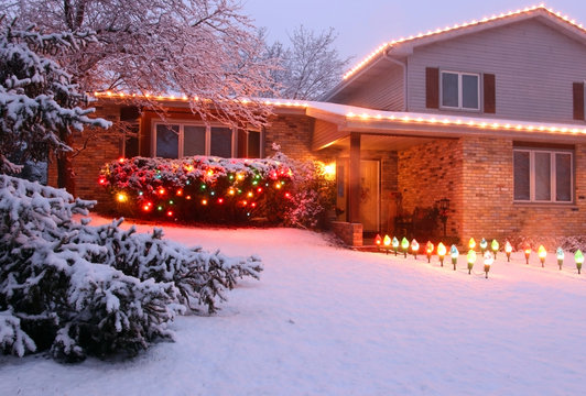 Beautiful winter blizzard evening view. Front yard of the private house covered by snow and decorated for winter holiday season glowing in the night. Christmas and New Year background.