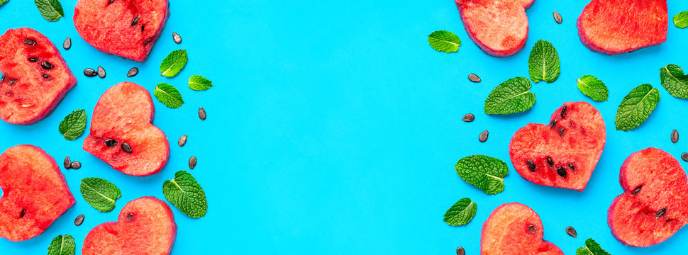 Creative summer food concept. Frame of Juicy slices of ripe red watermelon in the shape of a heart and mint leaves on blue background. Flat lay, top view, copy space. Watermelon pattern