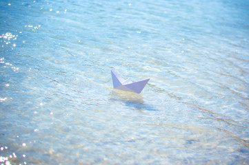 paper boat on the waves of blue water