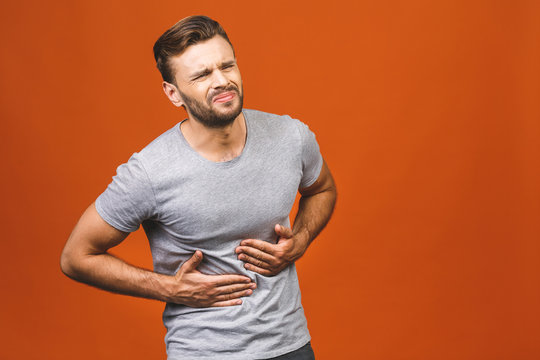 Man in pain holding his hurting stomach isolated on the orange background. Abdominal pain.