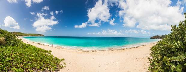 Panorama picture of white sandy beach and turquoise waters on carrebian island of St. Maarten