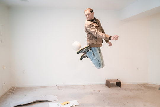 Young skilled man jumping up in mid-air performing trick with soccer ball playing sports goofy inside dirty basement room having fun