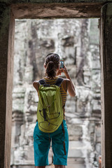 Rear view of woman taking picture with smartphone at Bayon, Ankor Thom temple