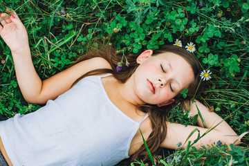 Young Girl with Daisy Flower Crown Resting in a Field of Clover