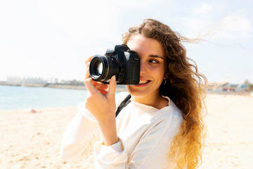 Happy young woman taking pictures in Barcelona beach