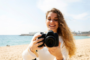 Smiling young woman taking pictures in Barcelona beach