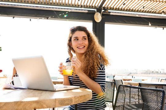 Young  woman working and drinking glass of orange juice