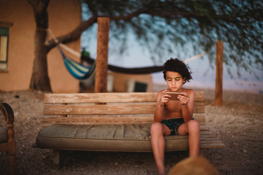 A young boy playing with his smartphone sitting on a bench in desert